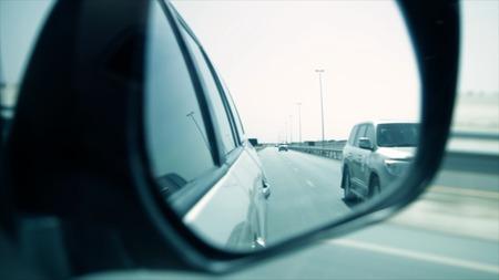 Foto de Close-up shot of a side rear view mirror of car. Stock. Side view mirror view of cars driving behind on a highway. - Imagen libre de derechos