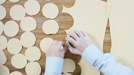 Cutting Dough into circles, top view. Scene. Preparation Meat Dumplings. Roll out the dough and cut circles out of it. Cutting dough circles. Male hands cut out dough circles