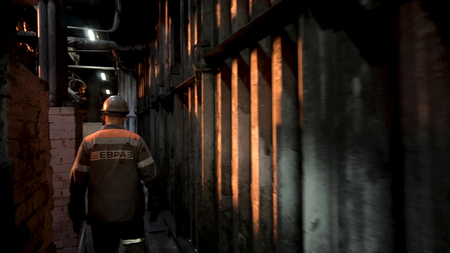 Photo pour Rear view of foundry worker wearing uniform and walking through the corridors of the metallurgical plant. Stock footage. Male walking at the factory. - image libre de droit