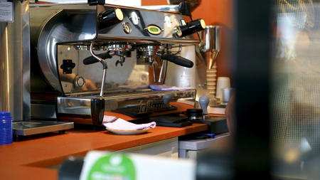 Photo pour Barista at professional coffee machine in coffee shop. Art. Barista washes and wipes espresso machine before making cup of coffee in cafe. - image libre de droit