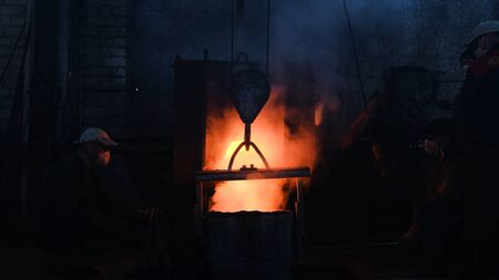 Photo pour Workers poured molten metal at plant. Stock footage. Workers in form and helmets control process of pouring molten metal from boiler at metallurgical plant - image libre de droit