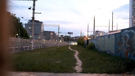 Foto de View of trail next to railway. Stock footage. Empty footpath in grass next to railroad in suburbs. Evening lights of city on background of path at railway with concrete walls in graffiti - Imagen libre de derechos