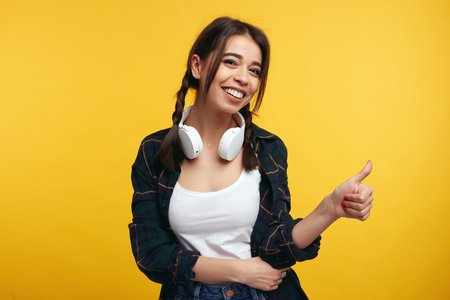 Portrait of happy teenager keeps thumb raised, being in good mood, shows her agreement, poses over yellow background. Young girl with headphones shows like gesture, satisfied with something.