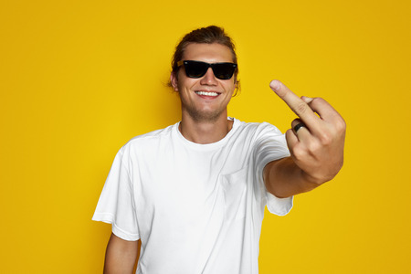 Foto für Indoor shot of young brutal man shows middle finger and smiles, shows his dislike or discontent with something, wears white t shirt, says Fuck you. Male hipster isolated on yellow background - Lizenzfreies Bild