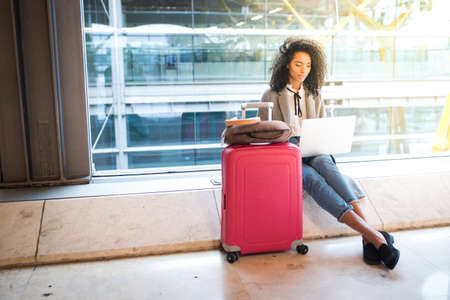 Photo pour black woman working with laptop at the airport waiting at the window - image libre de droit