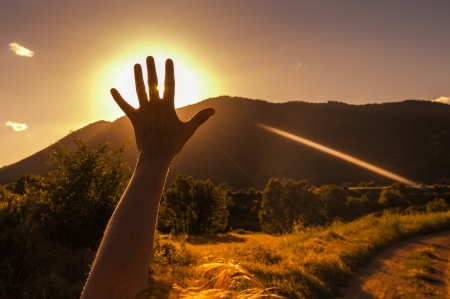 Photo for Girl raising her hand in front of the sun and the mountains - Royalty Free Image