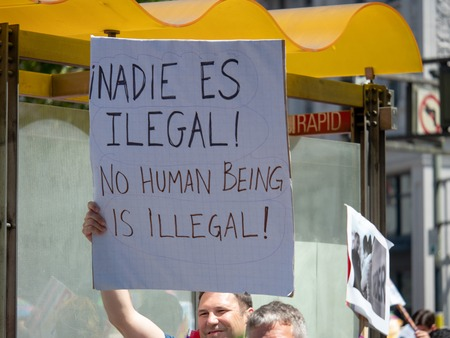 Pro-immigration sign on display by a marcher in a LBGT pride parade. No human being is illegal.