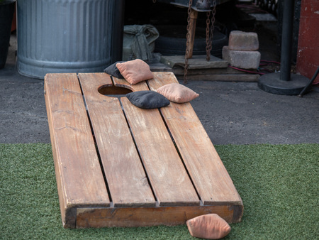 Photo pour Sets of beanbags in competitive game of cornhole on a lumber platform - image libre de droit