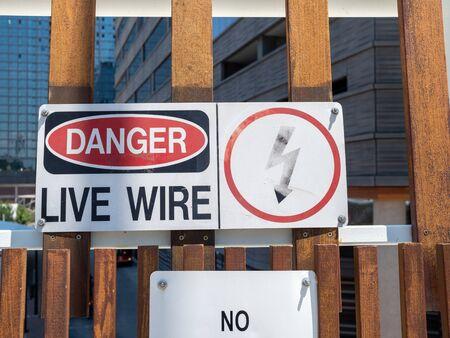 Danger live wire power lightning bolt warning sign posted near hazard