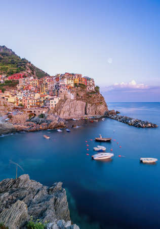 Photo for Long exposure shot of Manarola with Rock in the foreground in Cinque Terre, Italy during sunset hours - Royalty Free Image