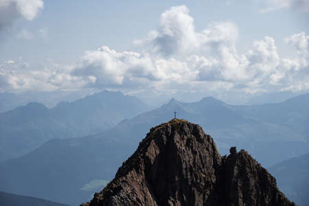 Photo pour The summit of a high mountain with a summit cross in the background a mountain panorama with clouds - image libre de droit