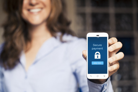 Photo pour Smiling woman showing her mobile phone. Secure payment message on the screen. - image libre de droit