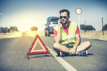 Man sitting on the asphalt in the middle of the road. He is talking to the assistance by phone.