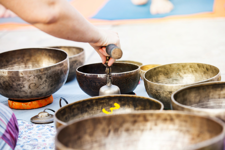 Detail of tibetan bowls being played during meditation and yoga session.