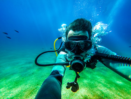 Photo pour Man taking a photo of himself, while floating in the ocean floor for scuba diving. - image libre de droit