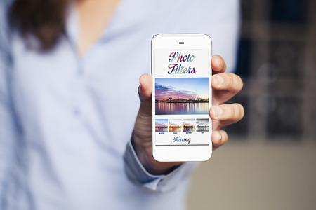 Woman holding a mobile phone with photo filters app on the screen. Generic app template design.