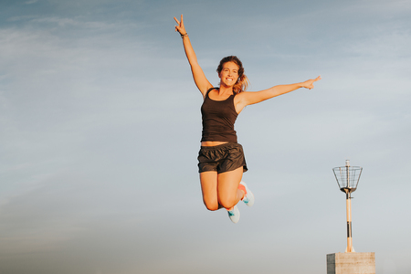 Photo pour Blonde girl jumping and doing victory sign. - image libre de droit