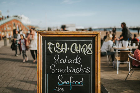 Foto de Blackboard with restaurant menus and information in the middle of a promenade, with Fish and Chips, salads, sandwiches and other food. - Imagen libre de derechos