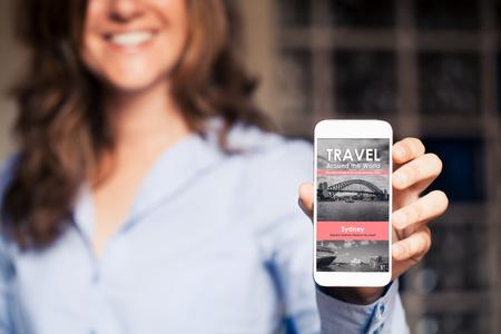 Foto de Smiling woman holding a mobile phone with travel news website in the screen. - Imagen libre de derechos