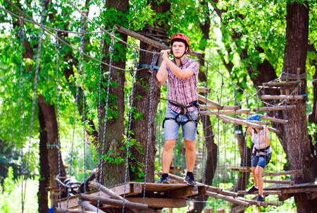 Photo pour adventure climbing high wire park - people on course in mountain helmet and safety equipment - image libre de droit