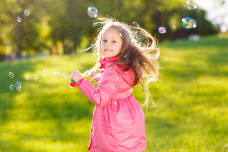 Photo pour The girls run and play with soap bubbles. - image libre de droit