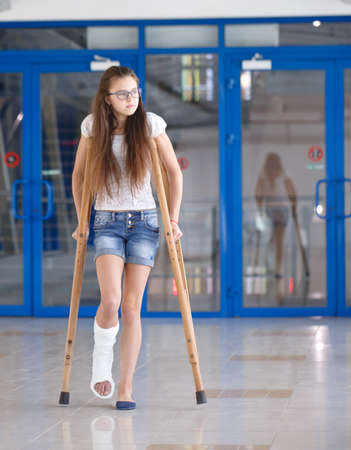 Photo pour A young girl is on crutches in the corridor of the hospital - image libre de droit