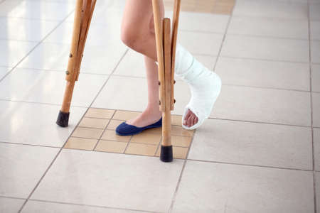 Photo pour A young girl is on crutches in the corridor of the hospital. - image libre de droit