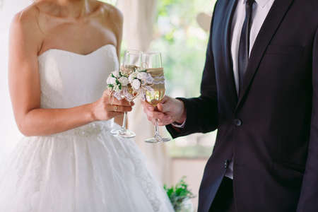 Bride and groom holding wedding champagne glasses
