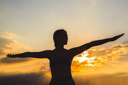 Photo for Silhouette of young woman practicing yoga or pilates at sunset or sunrise in beautiful mountain location, doing lunge exercise, standing in Warrior - Royalty Free Image