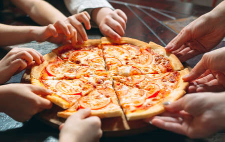 Photo pour Hands taking pizza slices from wooden table, close up view. - image libre de droit