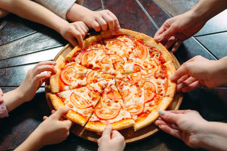 Photo pour Hands taking pizza slices from wooden table, close up view. - image libre de droit