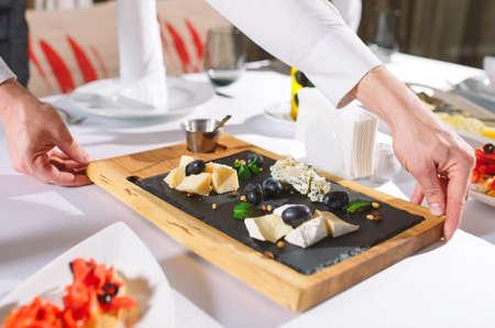 Photo pour Waiter serving table in the restaurant preparing to receive guests. - image libre de droit