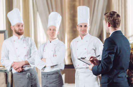Photo pour restaurant manager and his staff in kitchen. interacting to head chef in commercial kitchen - image libre de droit