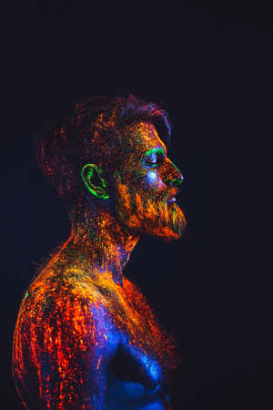 Photo for Concept. Portrait of a bearded man. The man is painted in ultraviolet powder - Royalty Free Image