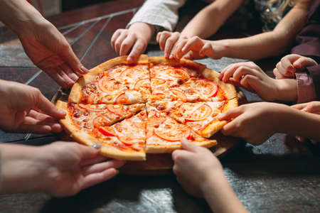 Photo pour Hands taking pizza slices from wooden table, close up view - image libre de droit