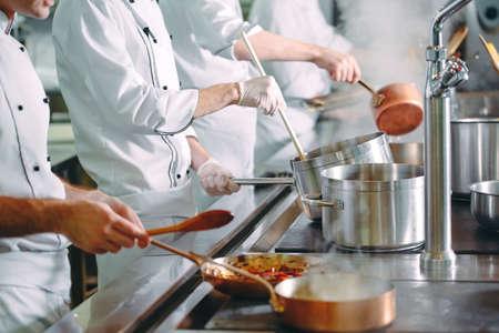 Foto de Chef cooking vegetables in wok pan. Shallow dof. - Imagen libre de derechos