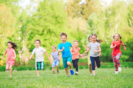 Foto de Many different kids, boys and girls running in the park on sunny summer day in casual clothes. - Imagen libre de derechos