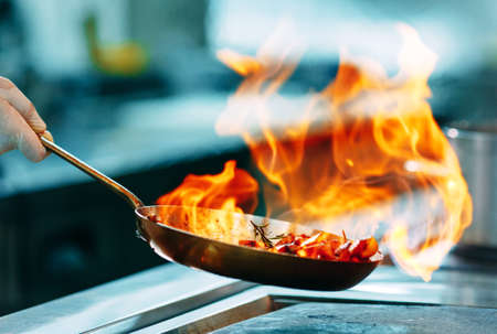 Photo pour Modern kitchen. Cooks prepare meals on the stove in the kitchen of the restaurant or hotel. The fire in the kitchen. - image libre de droit