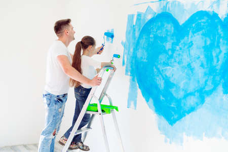 Photo pour Father and his little daughter painting a wall in new home. - image libre de droit