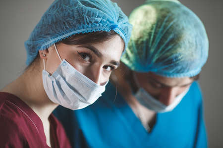 Photo pour Portrait of surgeons at work, operating in uniform, looking at camera. - image libre de droit