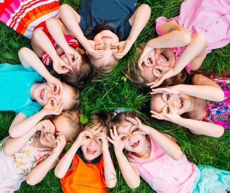 Photo pour A group of children lying on the green grass in the Park. The interaction of the children. - image libre de droit