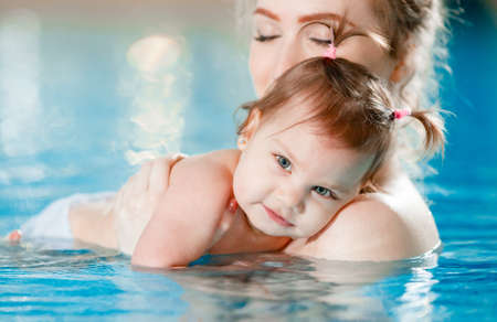 Photo pour Mom and baby swim in the pool. - image libre de droit