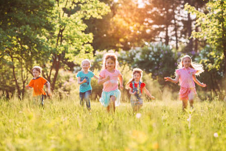 Photo pour Large group of kids, friends boys and girls running in the park on sunny summer day in casual clothes . - image libre de droit
