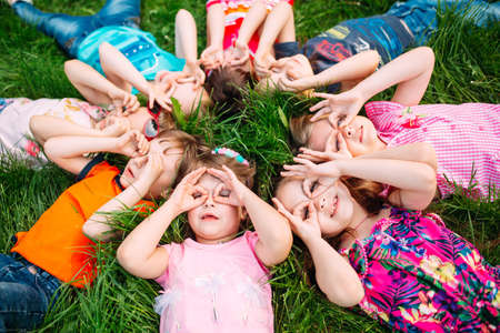 Photo for A group of children lying on the green grass in the Park. The interaction of the children. - Royalty Free Image