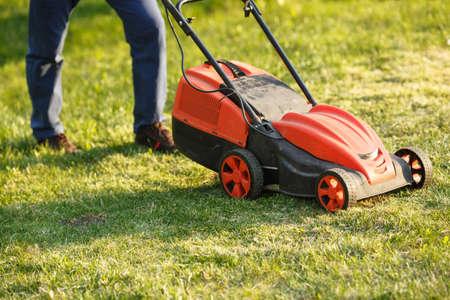 Foto de mowing trimmer - worker cutting grass in green yard at sunset. Man with electric lawnmower, lawn mowing. Gardener trimming a garden. - Imagen libre de derechos