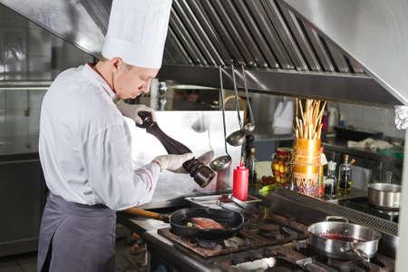 Photo pour Chef in restaurant kitchen at stove with pan, cooking. - image libre de droit