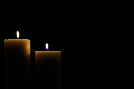 two candles lit with dark background