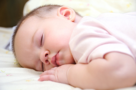 baby sleeping on the bed in a room