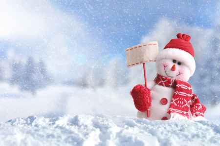 Winter arrival concept with Snowman with a blank placard in his hand. Dressed with red scarf and gloves and hat in the snow outside under the snow. Front view. Horizontal composition
