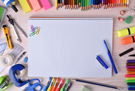 Background with school or office material with checkered notebook sheets in the center and space for title. Top view